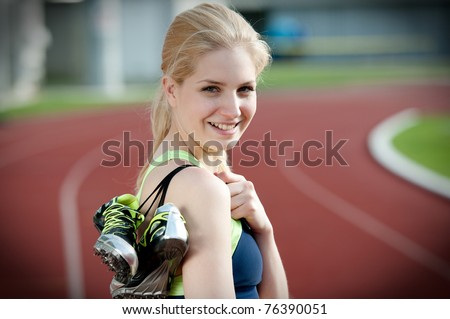 Portrait of a beautiful young female sprinter standing on a running track and holding her sprinting shoes with spikes