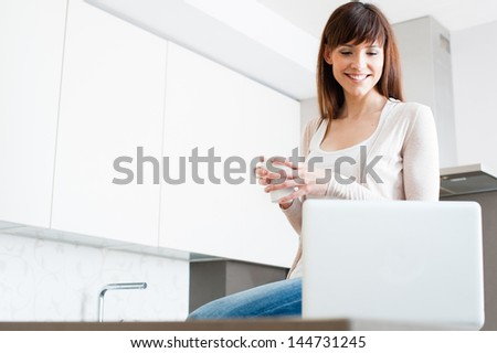 Portrait of a beautiful young female using a laptop at home.  A pretty woman taking a coffee while checking email on laptop