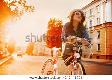 portrait of a beautiful young girl in a hat with a bicycle on city background in the sunlight outdoor - stock photo