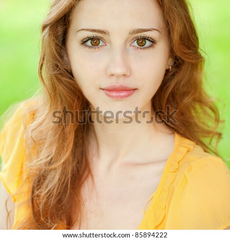 portrait of a beautiful young girl in a park on a background of green nature