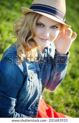 portrait of a beautiful young girl in a straw hat on a background of green grass Stock fotó ©