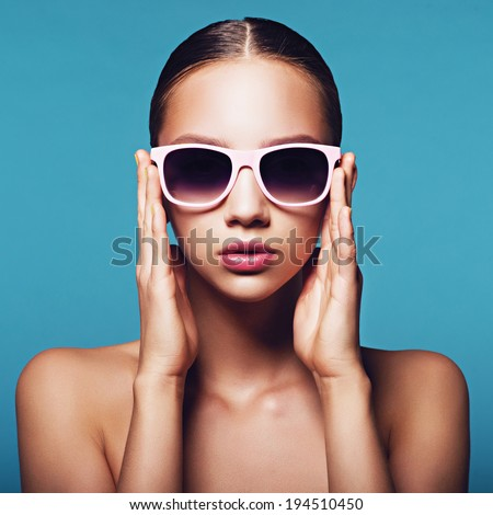 Portrait of a beautiful young girl in sunglasses on a blue background