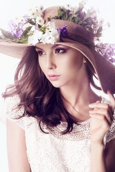 Portrait of a beautiful young girl in the studio with a hat with flowers in white dress