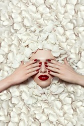 Portrait of a beautiful young girl in white rose petals. Red lips, red fingernails. The girl closes her eyes with her hands.Fashion, beauty, make-up, cosmetics, hairstyle, beauty salon, boutique.