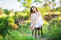 portrait of a beautiful young girl on chair, outdoors, in the field