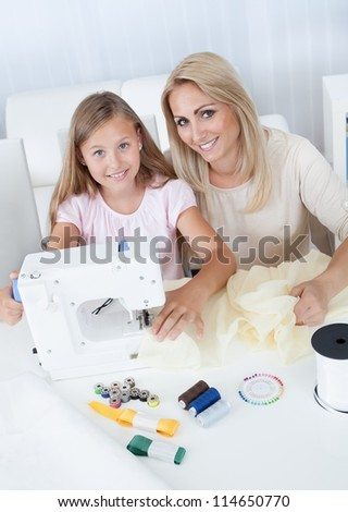 Portrait Of A Beautiful Young Girl Sewing With Her Mother At Home - stock photo