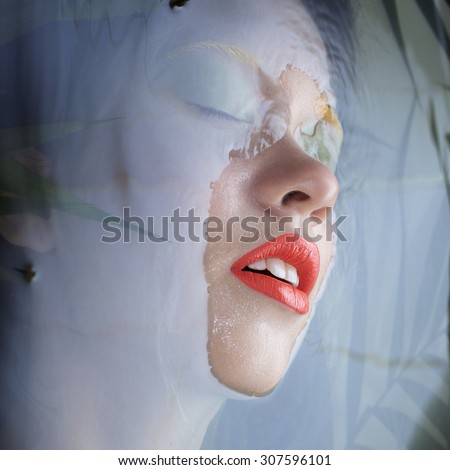 Portrait of a beautiful young girl sinks  wall of water. Bright orange lips fern leaves and mustard jacket. Closed eyes under water. Breathing. Harmony.