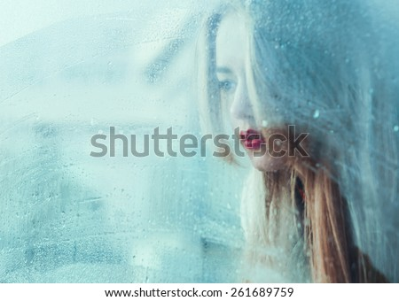 portrait of a beautiful young girl standing at the window watching the rain