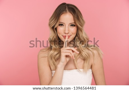 Portrait of a beautiful young girl with blonde curly hair standing isolated over pink background, showing silence gesture