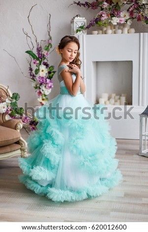 Stock Photo portrait of a beautiful young girl with blue eyes, make up and hairstyle in a lush turquoise dress in a studio with flower decoration