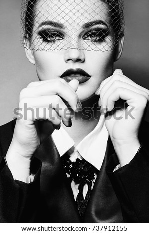 Portrait of a beautiful young girl with bright make-up and with a veil on her face. Black and white photo.