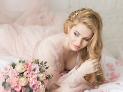Portrait of a beautiful young girl with long hair in transparent peignoir lies on bed next to bouquet of flowers. Morning of bride