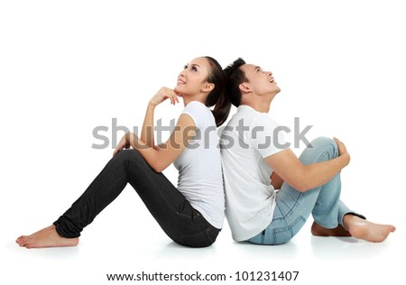 Portrait of a beautiful young happy couple sitting on the floor thinking something