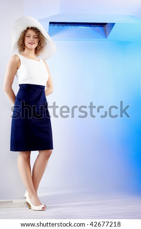 Portrait of a beautiful young lady in blue  apartment - stock photo