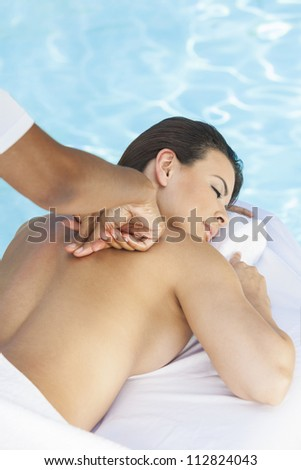 Portrait of a beautiful young Latina Hispanic woman eyes closed laying down, relaxing and having a massage by a swimming pool at a health spa