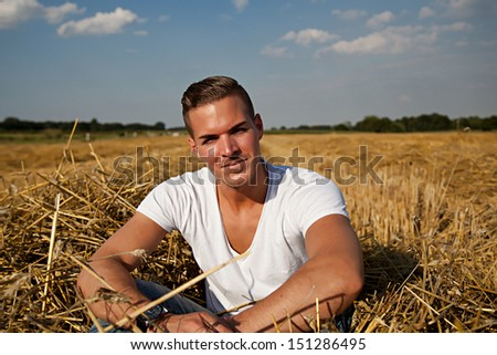 Portrait of  a beautiful young man outdoors in white casual shirt aitting on hay field