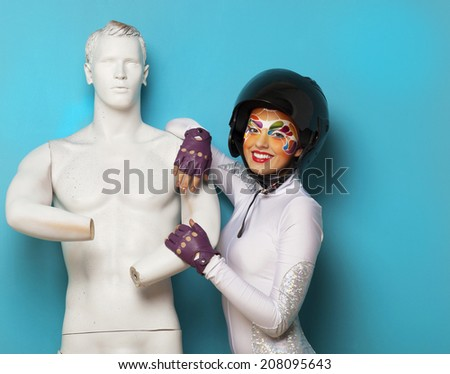 Portrait of a beautiful young model with bright creative make up with helmet and male dummy