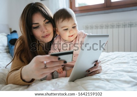Portrait of a beautiful young mom with a baby girl lying on the bed in a moment of intimacy while buying products online with the tablet and holding her credit card in hand - Millennial with daughter