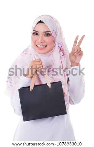 Portrait of a beautiful young muslim woman  in a holding in her hands a few shopping bags