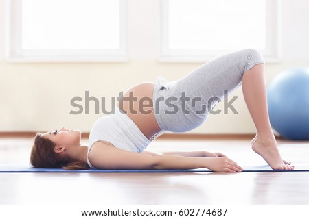 Portrait of a beautiful young pregnant woman holding her stomach while sitting near an exercise ball in the sport center. Working out, yoga and fitness, pregnancy concept.