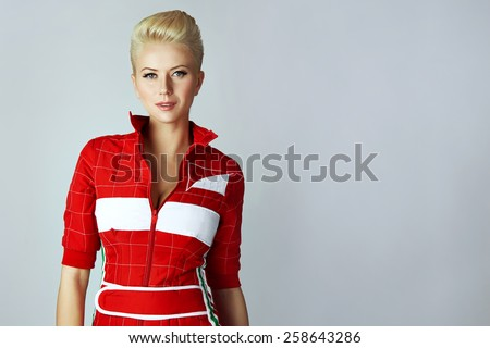 Portrait of a beautiful young sexy blond woman with short hair with a gentle make-up wearing a slinky red dress sporting well-groomed body and face golden tan