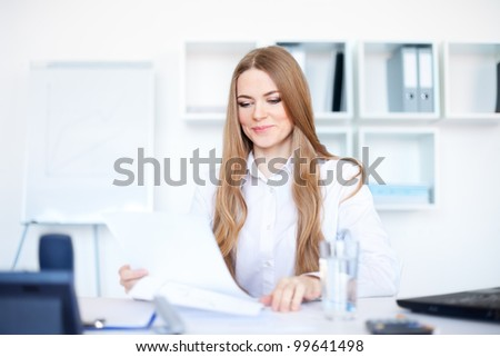 Portrait of a beautiful young smiling business woman doing some paperwork in bright office