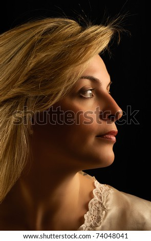 Portrait of a beautiful young woman against dark background, looking sideways