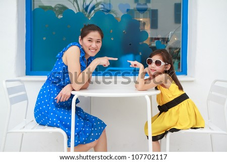 Portrait of a beautiful young woman and her daughter pointing to - stock photo
