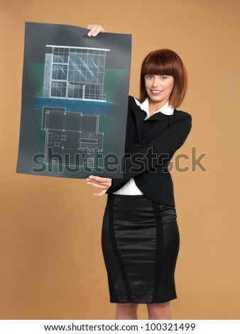 portrait of a beautiful, young woman architect, showing a blueprint, on beige background