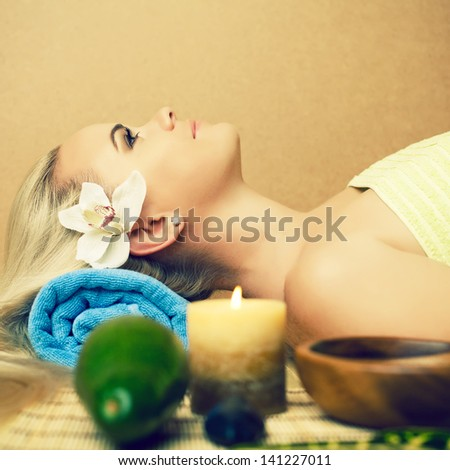 Portrait of a beautiful young woman at a spa salon. Perfect skin and long blond hair with white orchid. Skincare and haircare. Young skin. Close up. Copy-space. Indoor shot