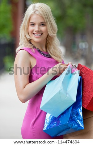 Portrait of a beautiful young woman carrying shopping bags