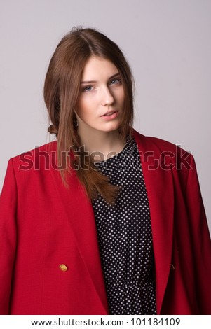 Portrait of a beautiful young woman dressed a polka dot dress and red jacket