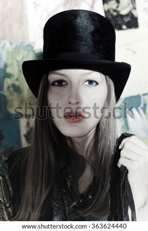 Portrait of a beautiful victorian style woman wearing a bowler hat and black  dress standing in front of country farm stables  172038d0e010