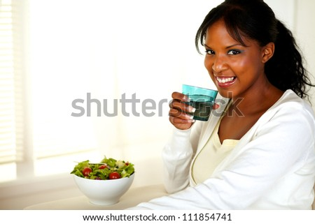 Portrait of a beautiful young woman drinking water and eating a healthy green salad while looking at you. With copyspace. #111854741