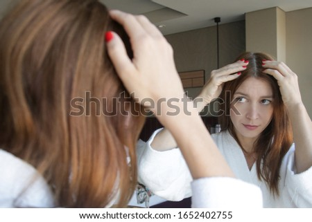 Portrait of a beautiful young woman examining her scalp and hair in front of the mirror, hair roots, color, grey hair, hair loss or dry scalp problem