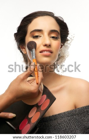 Portrait of a beautiful young woman having make up application