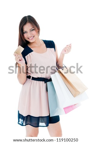 Portrait of a beautiful young woman holding shopping bags and credit card over white background