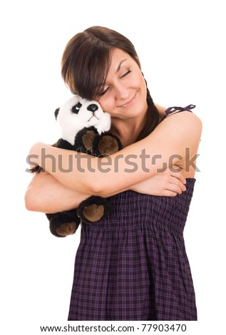 Portrait of a beautiful young woman hugging toy bear