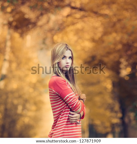 portrait of a beautiful young woman in a summer park. pictures in warm colors