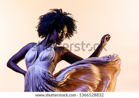 Portrait of a beautiful young woman in an elegant fancy dress that seems to float in the air