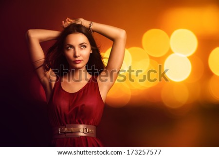 Portrait of a Beautiful Young Woman in Fashionable Red Dress over Bright Night Lights. Nightlife Party Concept. #173257577