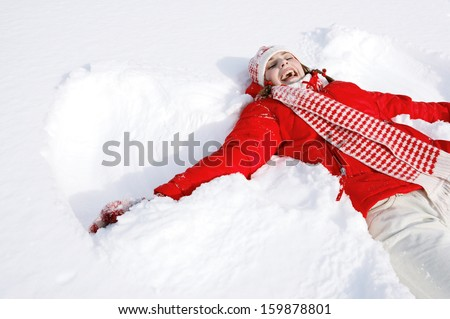 Stock Photo Portrait of a beautiful young woman laying down on a frozen snow lake moving her arms and legs up and down creating a snow angel figure, playing games during a sunny winter  vacation.