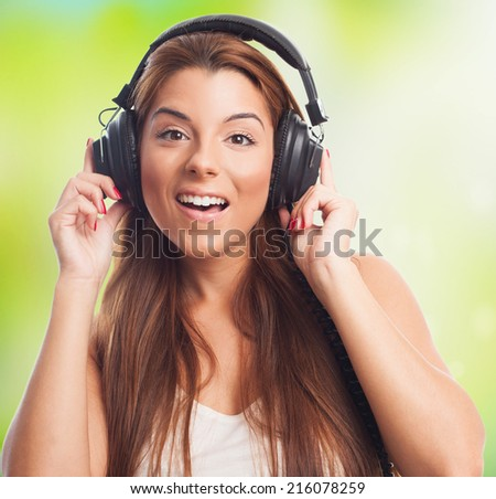 portrait of a beautiful young woman listening to music by headphones