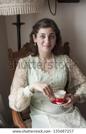 Portrait of a beautiful young woman looking directly at the camera. She is in a vintage dress and sitting in an antique chair holding her antique teacup and saucer.