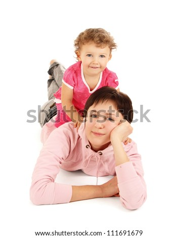 Portrait of a beautiful young woman lying on the floor with her daughter against white background