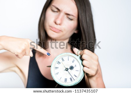 portrait of a beautiful young woman points at the clock strictly, isolated studio photo on a gray background #1137435107
