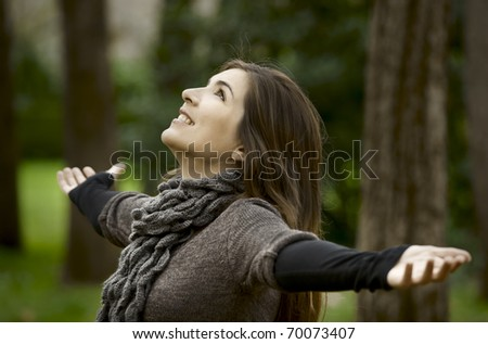 Portrait of a beautiful young woman relaxing with arms open and enjoying the nature