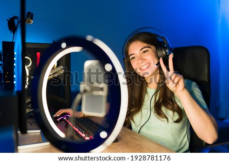 Portrait of a beautiful young woman saying hello to her online viewers during a live stream with a smartphone and a ring light. Smiling female gamer playing a video game in a gaming PC Photo stock ©