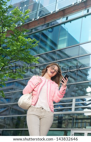 Portrait of a beautiful young woman sending a text message on mobile phone
