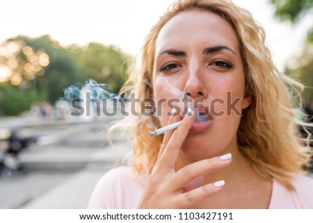 Portrait of a beautiful young woman smoking in the public park on a shiny bright day. #1103427191